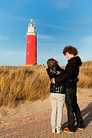 Red lighthouse at the Dutch island Texel with young couple