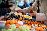 A man reaches across a row of fruit in an outdoor market to pay a vendor with a 10 Euro bill. Focus is tight on the bill changing changing hands. The ...