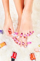 body part shot of healthy woman´s feet in pedicure toe separators. hand is putting polish on toenail