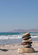 beautiful pebble stack on a sandy beach sea on the background