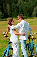 Romantic young couple with old bike in spring nature on sunny day