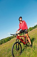 Young woman with mountain bike in spring nature on sunny day