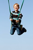 A happy child laughing on a swing