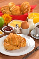 Delicious continental breakfast consisting of coffee, milk, orange juice, croissant, boiled egg, jam, butter and apple Selective Focus, Focus on the f...