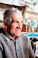 Indoor closeup portrait of an expressive senior farmer with selective focus