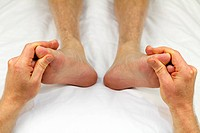 Big toes of both feet of an adult male receiving massage from a reflexologist as part of a treatment to promote circulation.