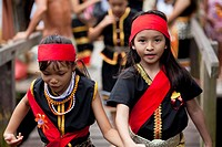 Young Bidayuh girls in traditional costumes running around Anna Rais Long House during Selamat Gawai Harvest Festival.