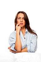 brunette thinking woman sitting in bed on white background