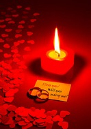 Two rings and a card with marriage proposal with a candle on the red background