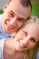 Closeup outdoors portrait of happy young smiling couple.