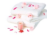 white towels with pink soap roses and candle on white background