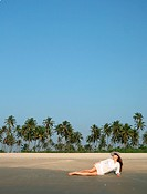 Woman in white hat lying on the beach in tropical country