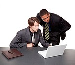 Isolated studio shot of two businessmen working on a laptop at a conference table.