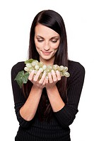 Isolated studio shot of a dark haired caucasian woman looking happily at a bunch of green grapes.