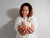 Smiling woman holding piggy bank in hands