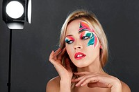 Beautiful young blonde woman with fantasy flowers creative make_up studio shot
