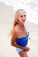 Portrait of a 57 year old woman on a beach looking at the camera