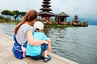 Mother and son enjoying views of beautiful Bali water temple at Bratan lake