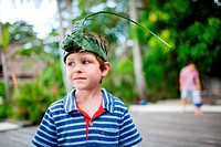 Portrait of cute little boy wearing crown made from palm leaves