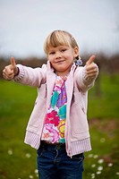 Cute little girl outdoors on a green field with thumbs up