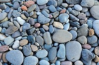 Close up of water eroded stones on beach filling frame