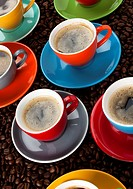 various cups of espresso in colorful cups upon coffee beans, tilted view