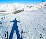 A shadow of ready to go downhill skier on empty fresh_made ski slope and mountains panorama on a background