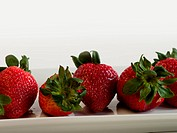 Fresh ripe strawberries on long white plate.
