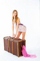 Young beautiful blonde with suitcase at white background