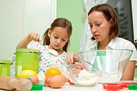 daughter helping her mother to bake a cake