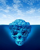 Hidden dangers with a deceptive hazardous iceberg floating in cold arctic ocean water with a small part of the frozen ice mountain above the sea and t...