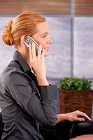 Businesswoman sitting in office lobby on mobile phone call, smiling, side view portrait.