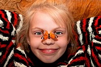 A little girl with butterfly on nose