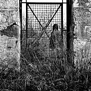 Man behind vintage metal door and overgrown plants in rural landscape.