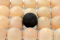 Group of wooden bolls same in size, colour, texture representing the crowd, a ball coloured in black higher than others and on focus representing diff...