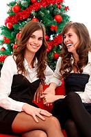 Two adorable women having fun by the Christmas tree