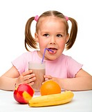 Cute little girl drinks fruit juice using drinking straw, isolated over white