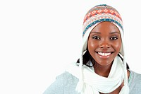 Smiling young woman with winter clothes on against a white background