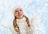 Christmas portrait of a beautiful happy girl with snowflakes on a winter background