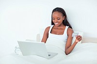 Young woman purchasing online in her bedroom