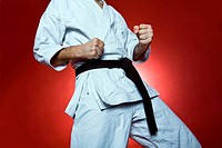 Young man practicing karate over red background