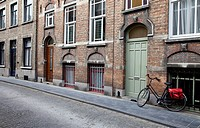 Old bicycle against brick wall. Bruges, Belgium
