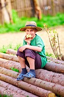 Portrait of a happy boy with a straw hat sitting on a pile of pine logs