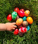 Child hand taking decorated Easter egg from grass