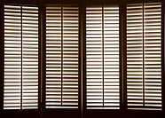 Wooden shutters in front of bright, sunlit windows