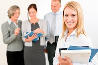 Business team attractive woman with happy colleagues discussing in back