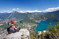 Mountain climber climbing the Via dell' Amicizia climbing route, view over the village of Riva and Lake Garda, Trentino, Italy, Europe