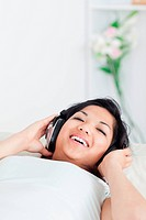 Smiling woman lying on a sofa with headphones on in a living room