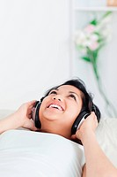 Smiling woman lying on a couch with headphones on in a living room
