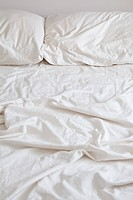 Empty bed with disheveled pillows and sheets